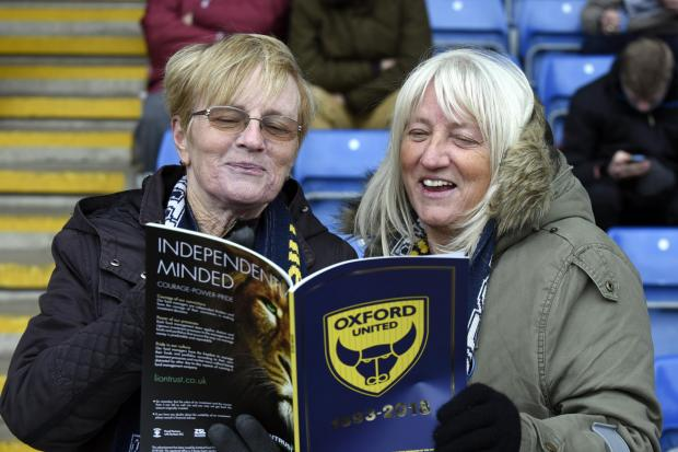 Oxford United fans read the special 125-year magazine before Saturday's game