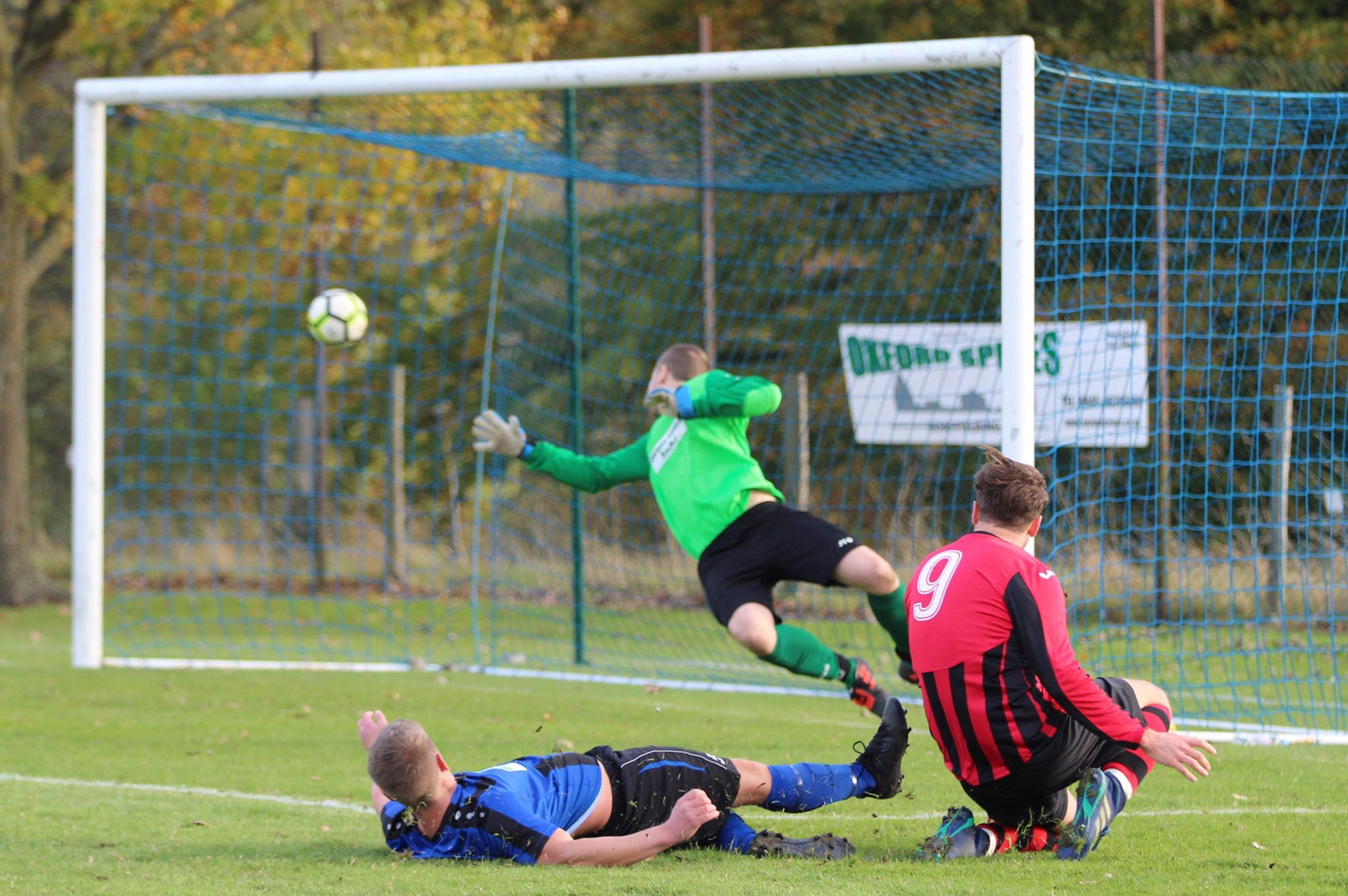 Berinsfield's Arran Colley (9) watches on as his shot beats the East Hendred goalkeeper during their 2-2 draw