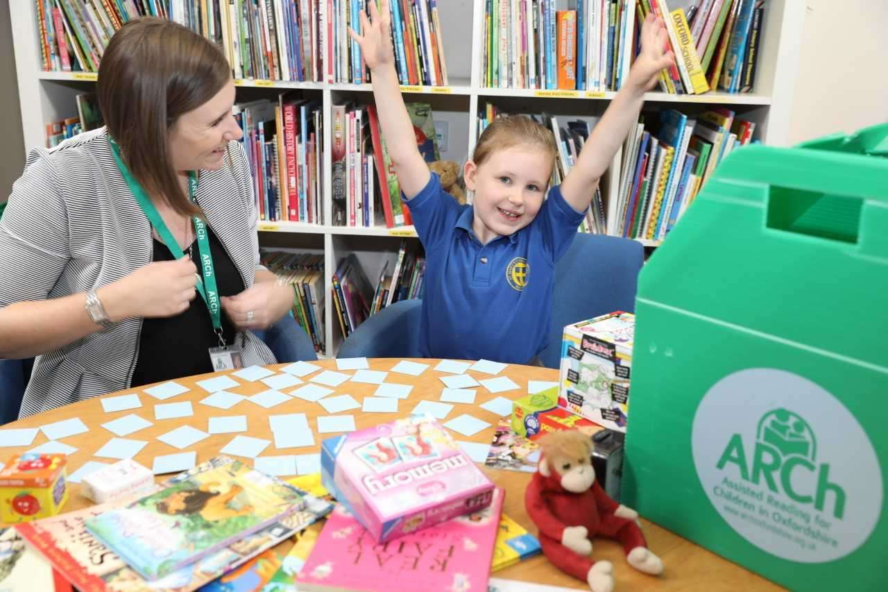 A school pupil learns alongside a volunteer from ARCh reading charity