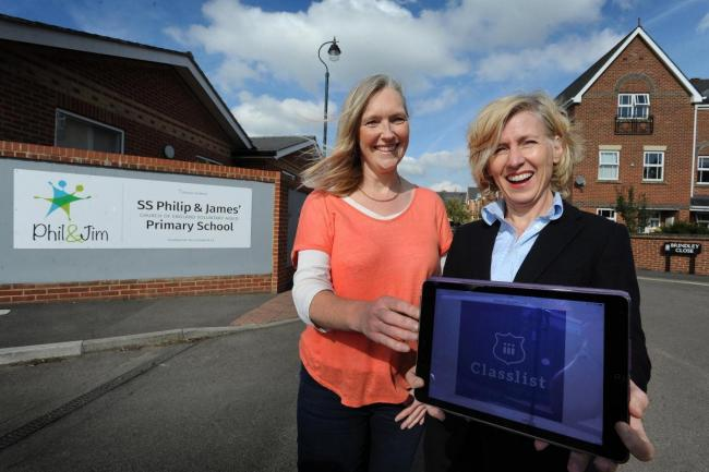 Clare Wright, left, and Susan Burton outside St Philip and St James Primary School, with the app. Pic: Jon Lewis