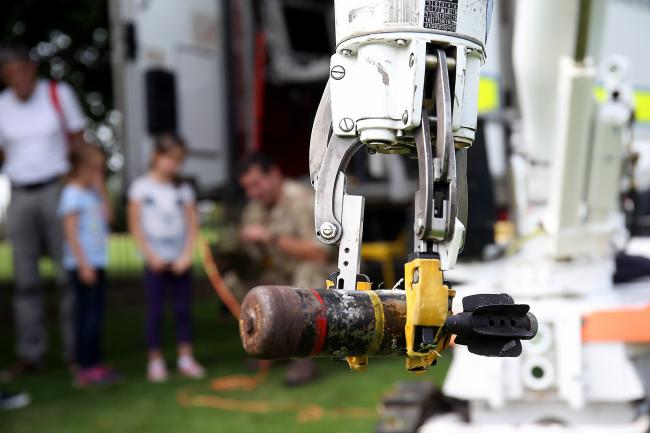Lance Corporal Blake Cookson shows nine year old Gabriela Popova the controls of a bomb disposal robot at an emergency services fun day in Edmonds Park, Didcot. Picture: Ric Mellis