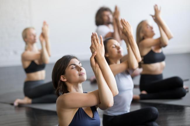 Group of young sporty people practicing yoga lesson, doing Cow Face exercise, Gomukasana pose, working out, indoor close up view, students training in club, studio.