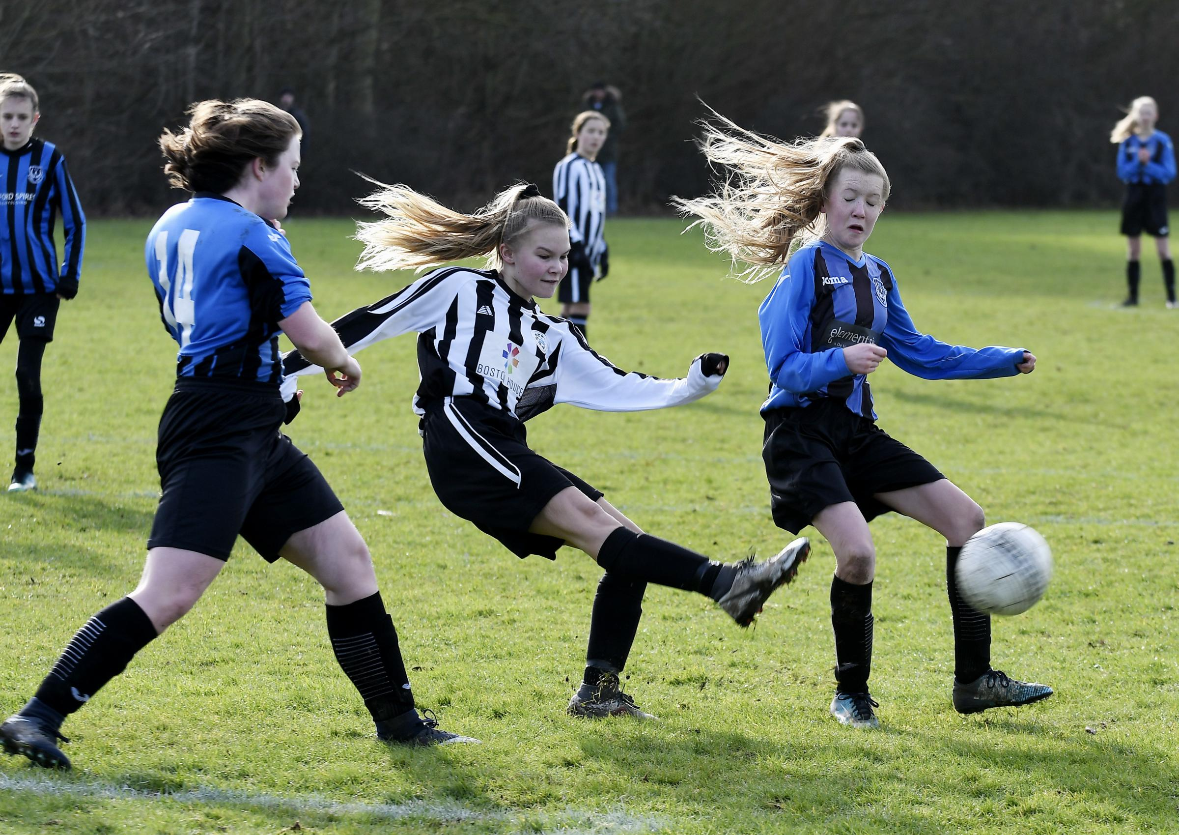 Harwell's Ellie White and Amber Hansen put pressure on Mya Stock as the Grove player shoots in their Under 15 clash Picture: David Fleming