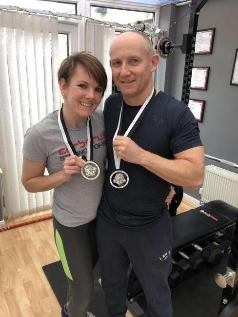 Lucy and Mark Anderson with their powerlifting medals