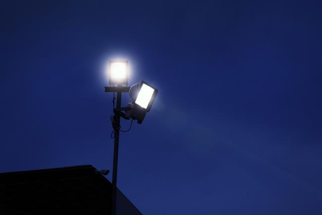 Floodlights and a CCTV camera provide security at a factory. Ample copy space on the dark blue nighttime sky..