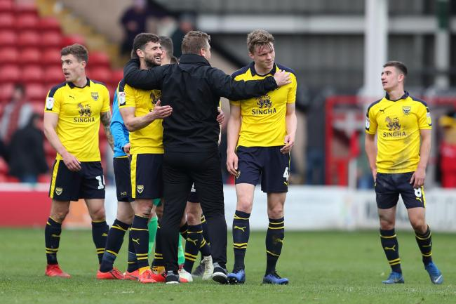 John Mousinho (second left) is hugged by Oxford United boss Karl Robinson after the win at Walsall   Picture: James Williamson