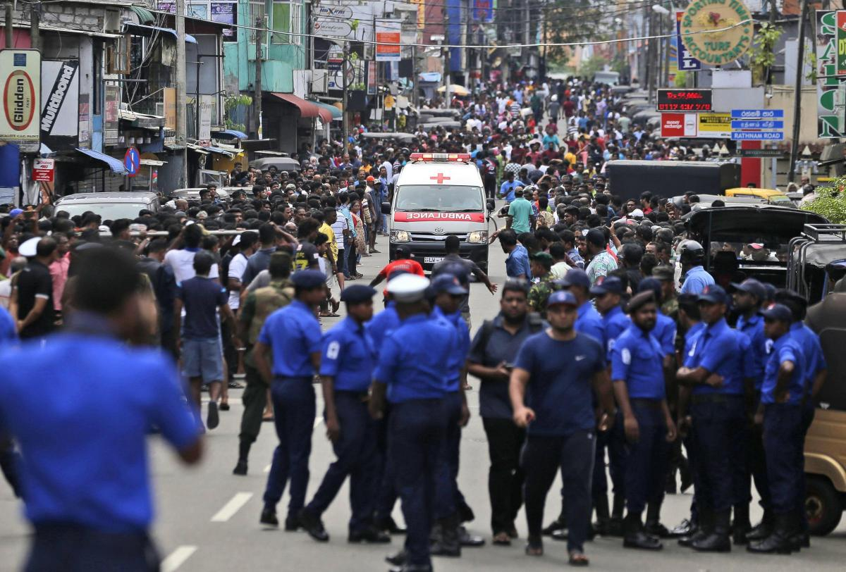 Police officers clear the road after explosions in Colombo. Picture: Press Association