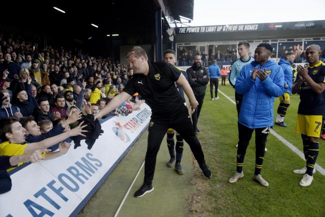 Karl Robinson shows his appreciation to the Oxford United supporters by handing over some momentos at full time on Saturday. Picture: David Fleming