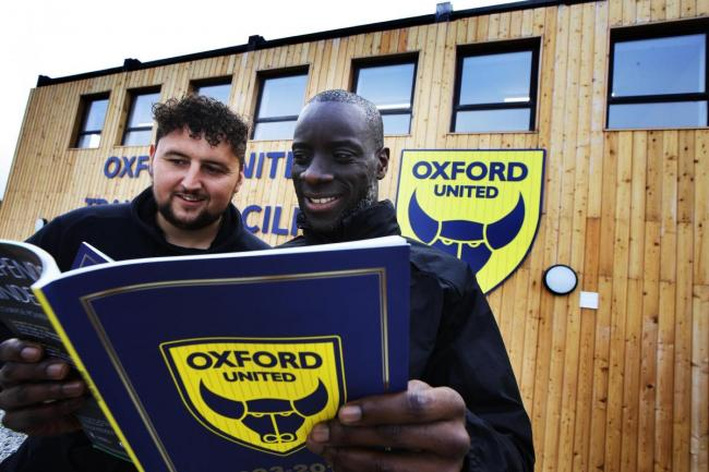 Leon Blackmore-Such and Chris Allen read the Oxford United 125th anniversary magazine Picture: Ed Nix